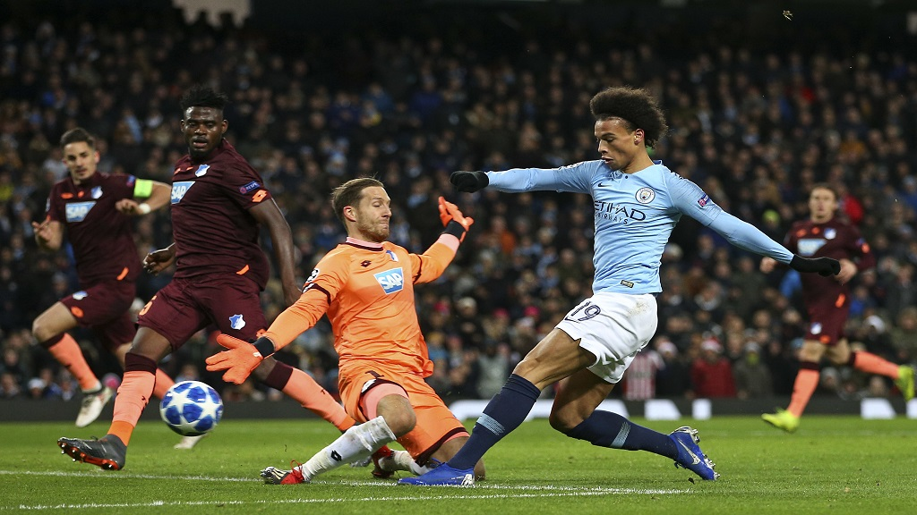 Manchester City midfielder Leroy Sane scores his second goal against Hoffenheim goalkeeper Oliver Baumann during the Champions League Group F football match at the Etihad stadium in Manchester, England, Wednesday, Dec. 12, 2018.