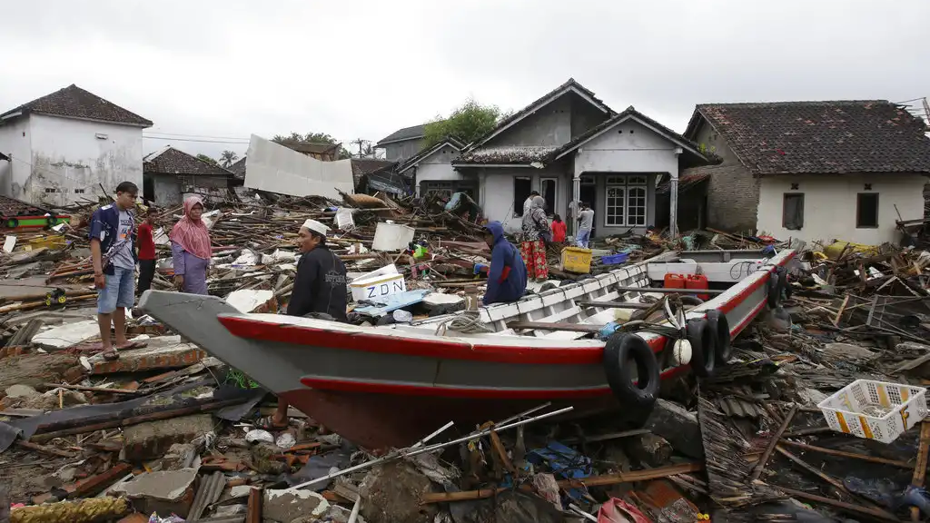 People inspect the damage at a tsunami-ravaged village in Sumur, Indonesia, Tuesday, Dec. 25, 2018. (AP Photo/Achmad Ibrahim)