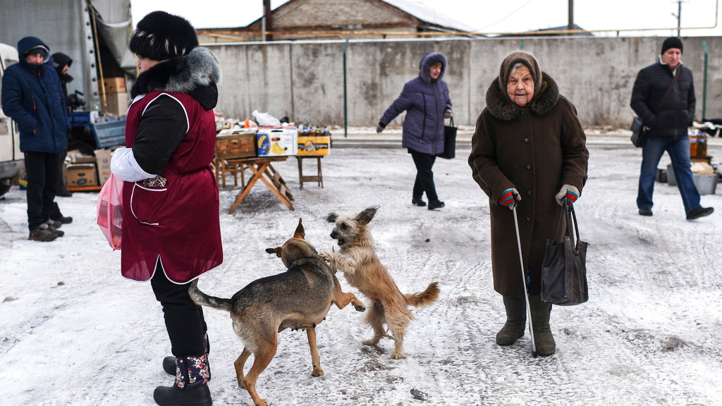 Local people walk through at Saturday's market in Milove, a small town at the border between Ukraine and Russia, in Luhansk region, eastern Ukraine, Saturday, Dec. 1, 2018. (AP Photo/Evgeniy Maloletka)
