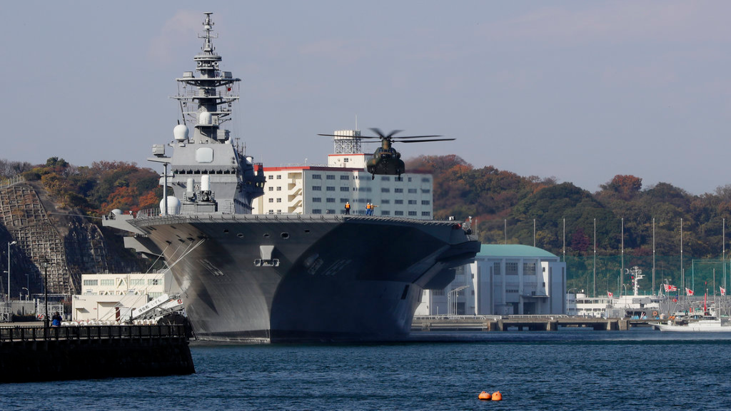 FILE - In this Dec. 6, 2016, file, photo, a helicopter of Japan Self-Defense Forces prepares to land on the flight deck of the helicopter destroyer Izumo of Japan's Maritime Self-Defense Force (JMSDF) following the visit by United States Secretary of Defense Ash Carter in Yokosuka, south of Tokyo. (AP Photo/Eugene Hoshiko, File)