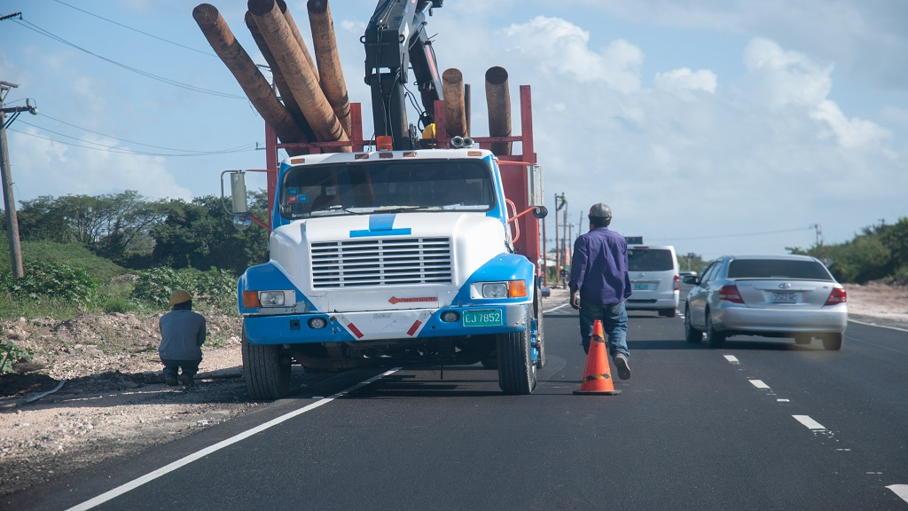 Members of a contracted work team engaged in mounting light poles along the new Three Miles bypass road in St Andrew on Thursday.