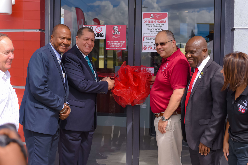 Industry Minister Audley Shaw (left center) participates in the ribbon cutting ceremony for the KFC Store opening in Falmouth. Sharing in the moment are (from left) Custos of Trelawny, Harold Paul Arnold Muschett, MP for Northern Trelawny,Victor Wright Jr., Managing Director of Restaurants of Jamaica, Mark Myers, Falmouth Mayor Colin Gager and Marketing Director for Restaurants of Jamaica,Tina Matalon.