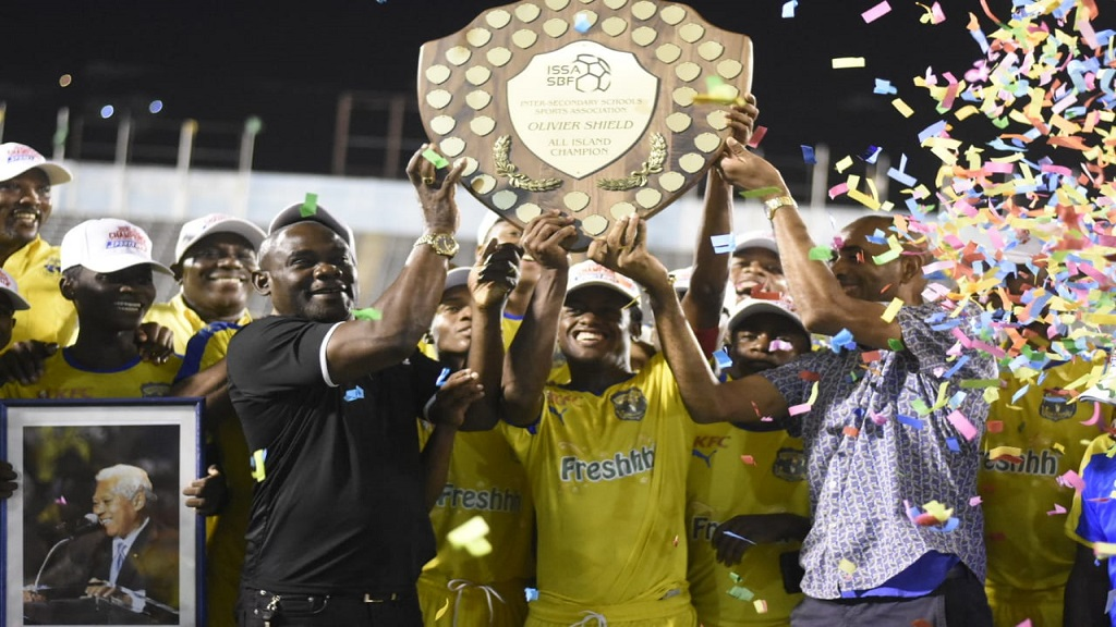 Dr Walton Small (left), president of the Inter-Secondary Schools Sports Association, presents the 2018 Olivier Shield to members of the Clarendon College team on Saturday, December 8, 2018 (PHOTOS: Marlon Reid.