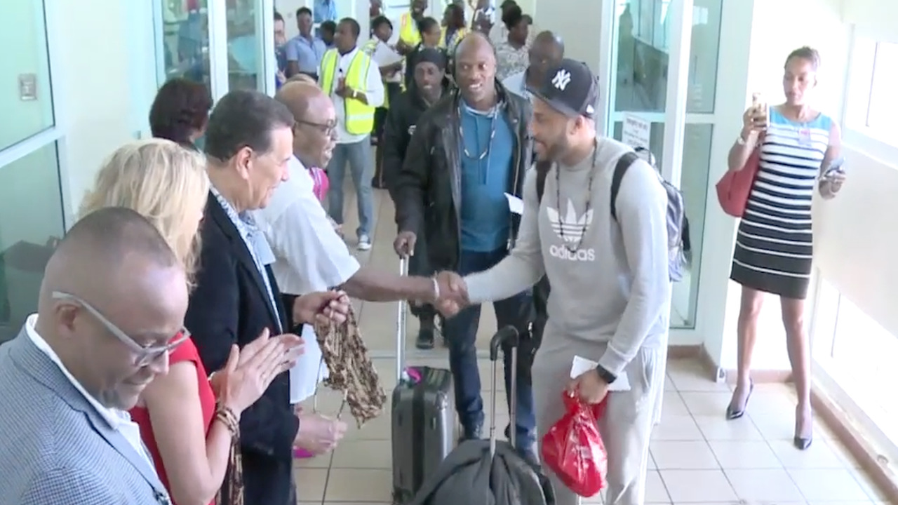 Tourism Minister shakes hands with a visitor who was among the passengers on Swoop's inaugural flight to Jamaica at the Sangster International Airport in Montego Bay. He is joined by Montego Bay Mayor Homer Davis;Swwop's communication executive Karen McIsaac and Tourism Director Donovan White.