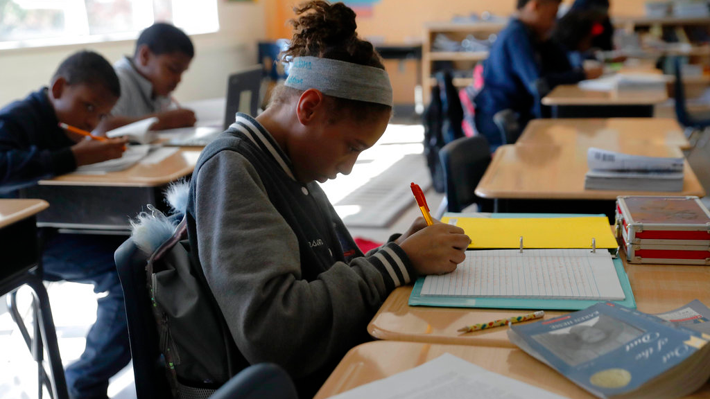 In this Tuesday, Dec. 18, 2018 photo, Breanna Johnson works on her assignment in her 6th grade english class at Alice M. Harte Charter School in New Orleans.  (AP Photo/Gerald Herbert)