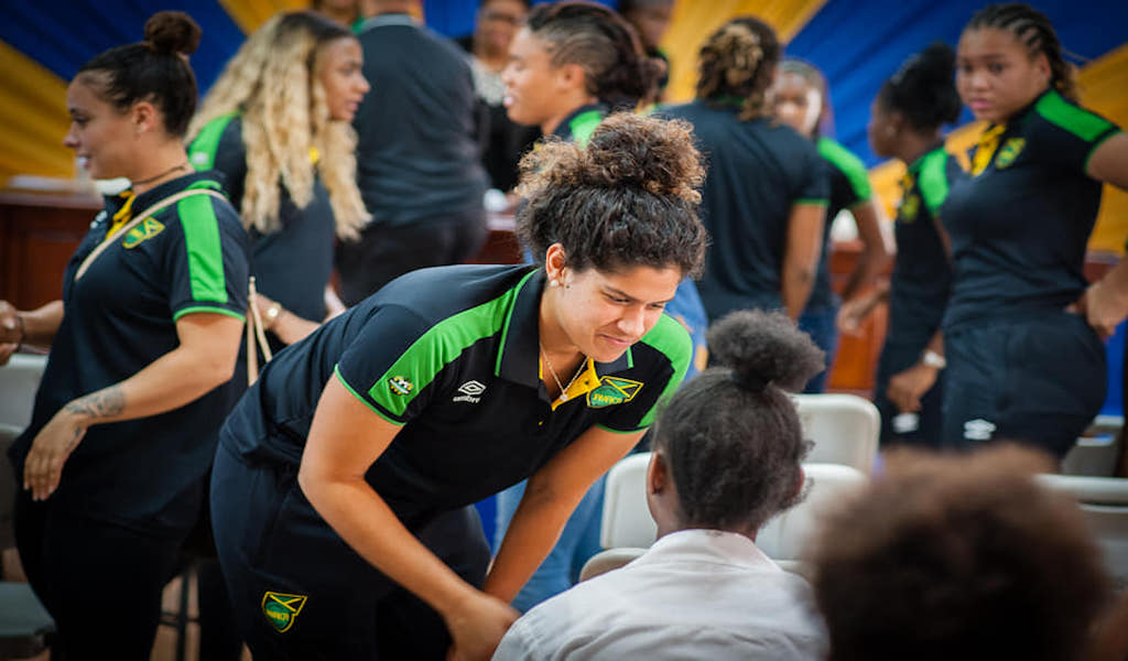 Jamaica national team member Marlo Sweatman talks to a girl during one of the series of activities organised by Government for the Reggae Girlz.