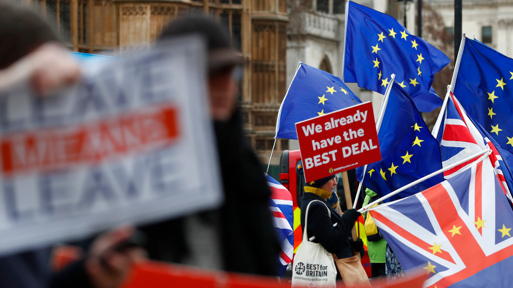 Pro and anti Brexit demonstrators wave their placards and flags outside the Houses of Parliament in London, Tuesday Dec. 18, 2018. (AP Photo/Alastair Grant)