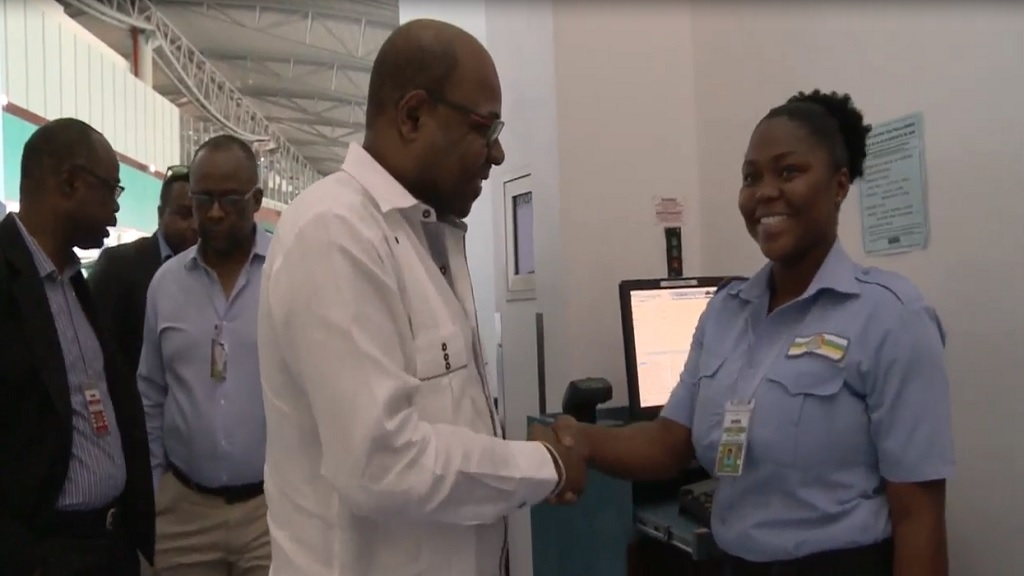 Tourism Minister Edmund Bartlett greets a member of staff at the Norman Manley International Airport.