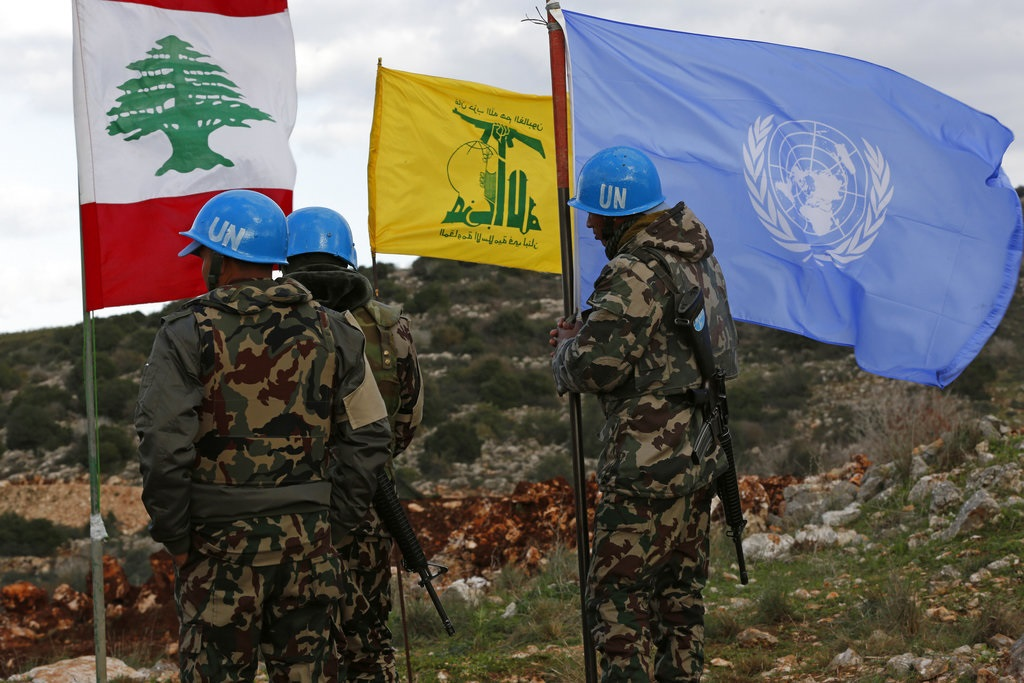 UN peacekeepers hold their flag while standing next to Hezbollah and Lebanese flags, at the site where Israeli excavators are working, near the southern border village of Mays al-Jabal, Lebanon.