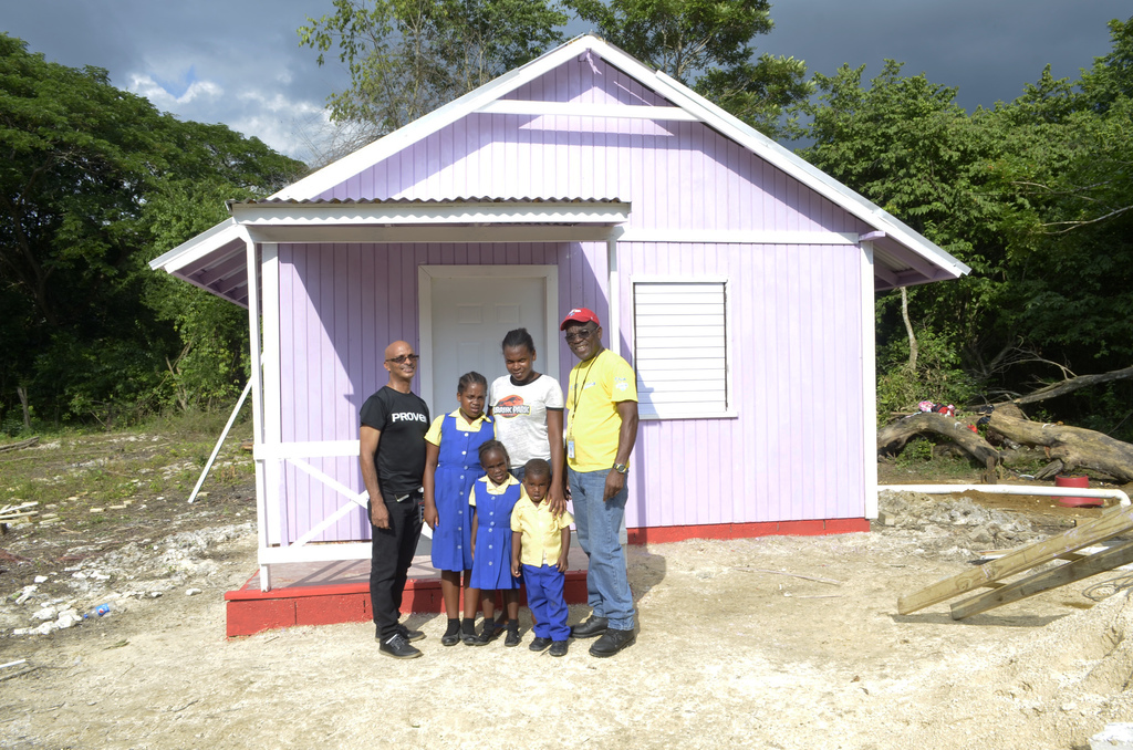 Proven Wealth Branch Manager (Mandeville) Paul Ebanks (left), Feone Hutchinson (centre), her three children and Food for the Poor Regional Director, Paul Ferron (right) at the handover of the new home.
