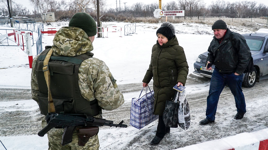 Ukrainians cross the border from Russia to Ukrainian side of the Ukraine - Russia border in Milove town, eastern Ukraine, Sunday, Dec. 2, 2018. On a map, Chertkovo and Milove are one village, crossed by Friendship of Peoples Street which got its name under the Soviet Union and on the streets in both places, people speak a mix of Russian and Ukrainian without turning choice of language into a political statement. (AP Photo/Evgeniy Maloletka)