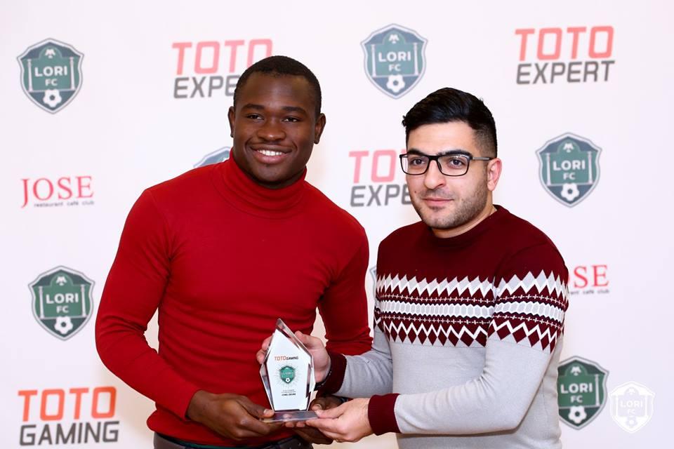 Jonel Desire et un représentant de TotoGaming  au moment ou l'attaquant haïtien recevait son trophée. Photo: FC Lori