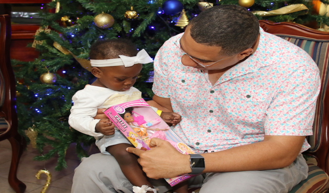 Prime Minister Andrew Holness gifts this child with a toy at the OPM's Christmas treat on Sunday. (PHOTOS: Llewellyn Wynter)