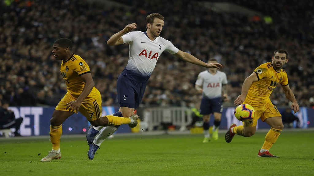 Tottenham Hotspur's Harry Kane, centre falls as he is clipped by Wolverhampton Wanderers Ivan Cavaleiro, left, during their English Premier League football match at Wembley stadium in London, Saturday, Dec. 29, 2018.