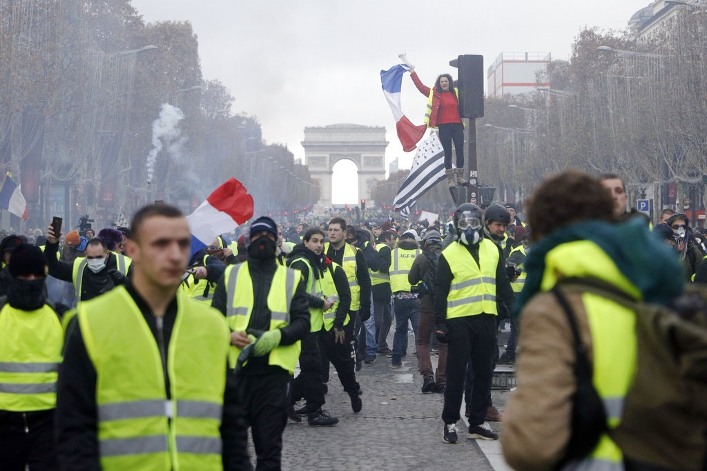 "In this Nov. 24, 2018, file photo, demonstrators march on the famed Champs-Elysees avenue in Paris, France, as they protest the rising of the fuel prices. ""Yellow vest"" protests have gripped France for four weeks, blocking highways from Provence to Normandy and erupting in rioting in Paris. They've shaken the country to its core and left President Emmanuel Macron struggling to retain control. (AP Photo/Kamil Zihnioglu, File)"