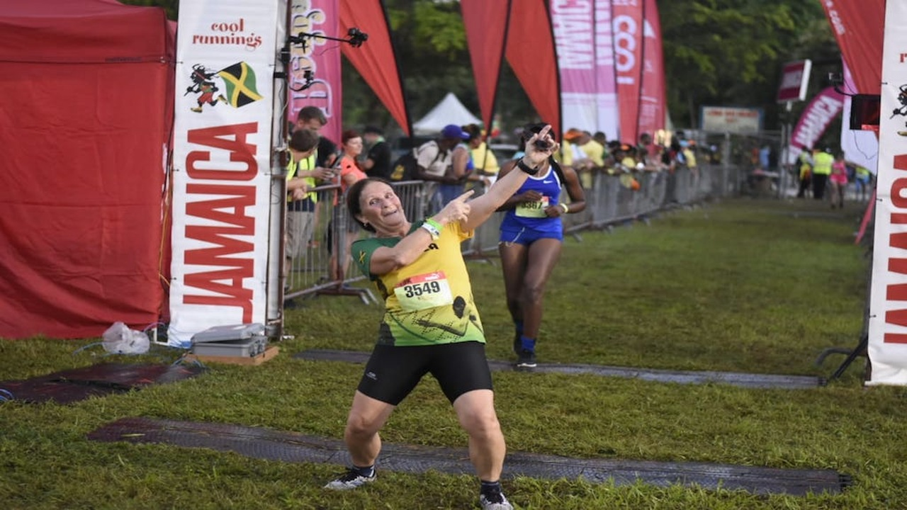 A woman gives her best impression of Usain Bolt's 'To the World' pose  after completing her race at the Reggae Marathon on Sunday. (PHOTO: Marlon Reid)
