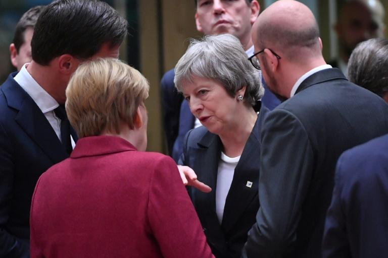 La Première ministre britannique Theresa May passe derrière le président de la Commission européenne Jean-Claude Juncker au sommet européen de Bruxelles, où elle est venue chercher de l'aide pour faire passer l'accord de Brexit, le 13 décembre 2018