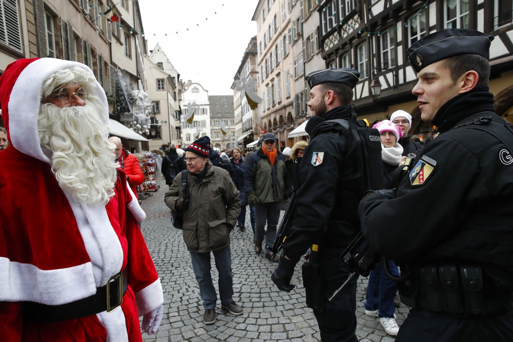 A man dressed like a Santa Claus watches police officers patrolling near the Christmas market reopens in Strasbourg, eastern France, Friday, Dec.14, 2018.