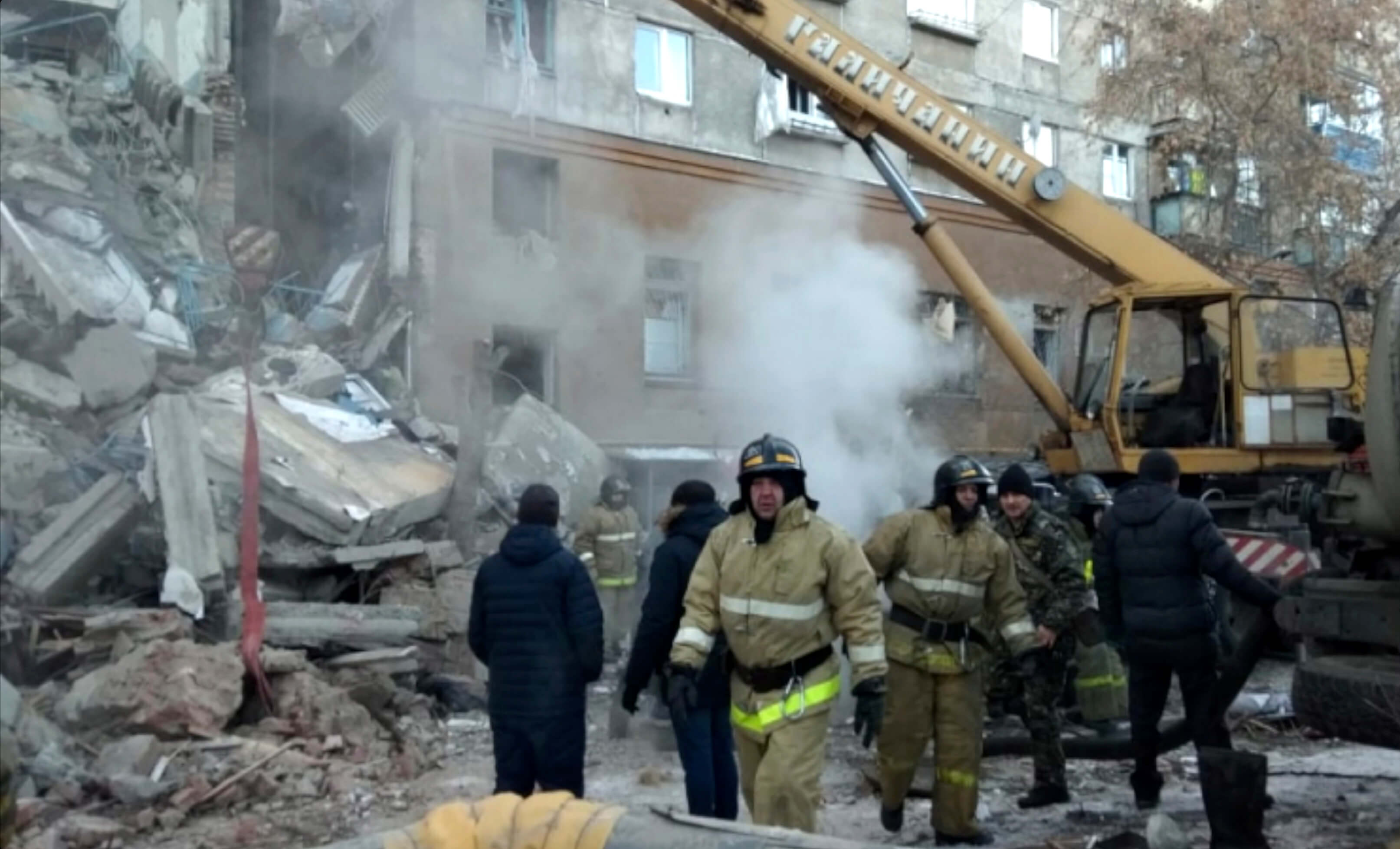 This photo provided by the Russian Emergency Situations Ministry taken from tv footage shows Emergency Situations employees working at the scene of a collapsed section of an apartment building, in Magnitigorsk, Russia, Monday, Dec. 31, 2018. (Russian Ministry for Emergency Situations photo via AP)