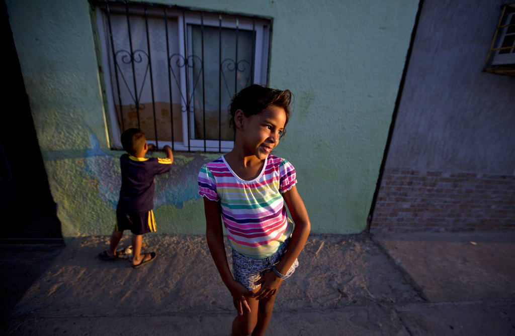 "In this Dec. 10, 2018 photo, Solgreidy, 8, and her 3-year-old brother Elvis stand outside of their uncle's home in Punto Fijo, Venezuela. ""I told her goodbye,"" Solgreidy said, crying. ""And since then I haven't seen her again."" (AP Photo/Fernando Llano)"