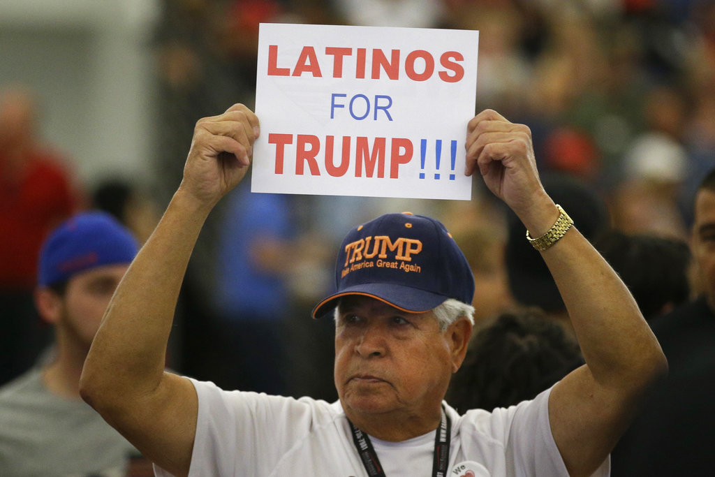 In this May 25, 2016 file photo, a man holds up a sign for then-Republican presidential candidate Donald Trump before the start of a rally at the Anaheim Convention Center, Wednesday, May 25, 2016, in Anaheim, Calif. Republicans are holding onto a steady share of the Latino vote in the Trump era.