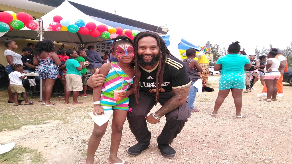 Ky-Mani Marley and a little child pose for a photo opportunity during Friday's treat at the Elleston Wakeland Youth Centre in Falmouth, Trelawny.