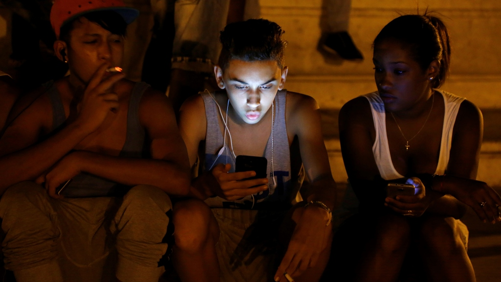 In this July 1, 2015 file photo, youths use a password protected wifi network coming from a five star hotel to surf the Internet on their smart phones in downtown Havana, Cuba. Cuba's government announced on Tuesday, Dec. 4, 2018 that its citizens will be offered full internet access on mobile phones starting Thursday, Dec. 6, becoming one of the last nations to do so. (AP Photo/Desmond Boylan, File)