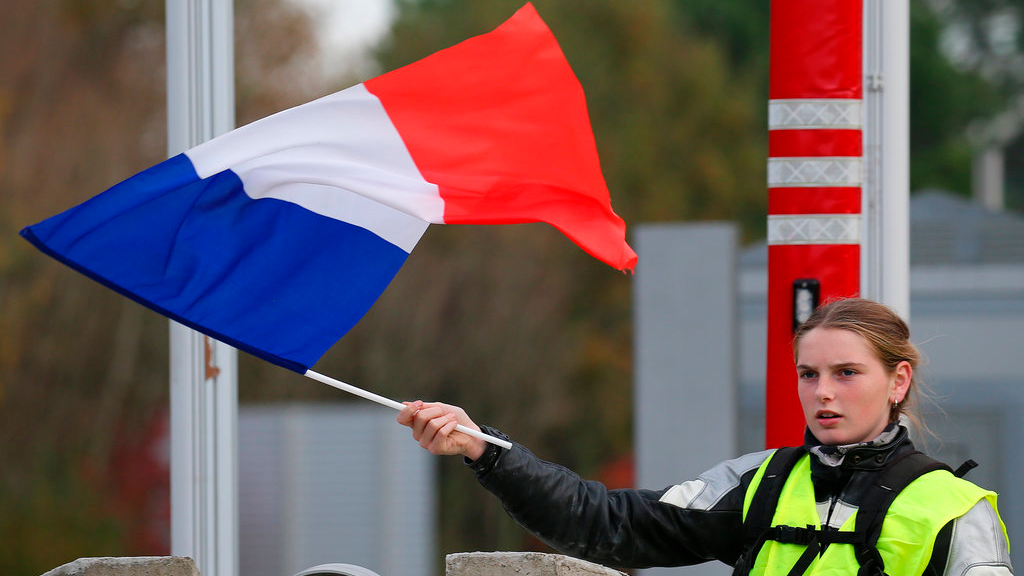 A demonstrator holds a french flag at the toll gates on a motorway at Biarritz southwestern France, Wednesday, Dec. 5, 2018.(AP Photo/Bob Edme)