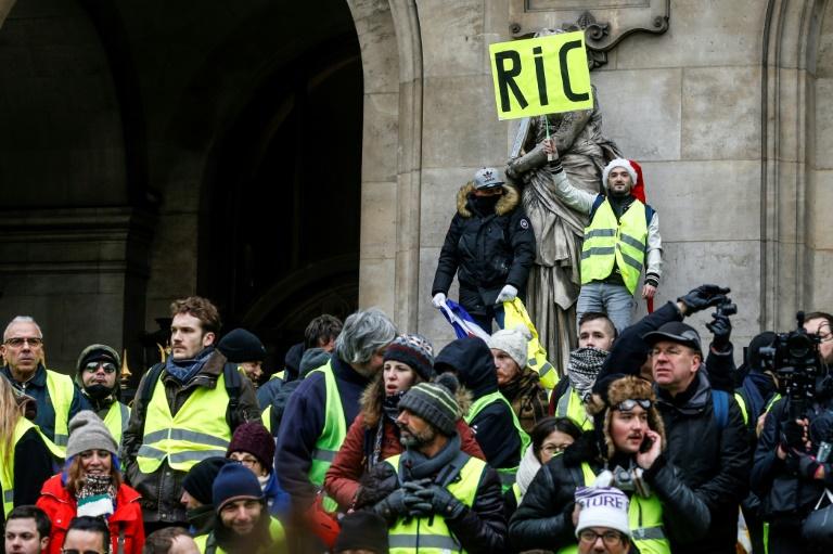 """Des """"gilets jaunes"""" forment une pyramide humaine dans la manifestation sur les Champs-Elysées à Paris, le 15 décembre 2018"""