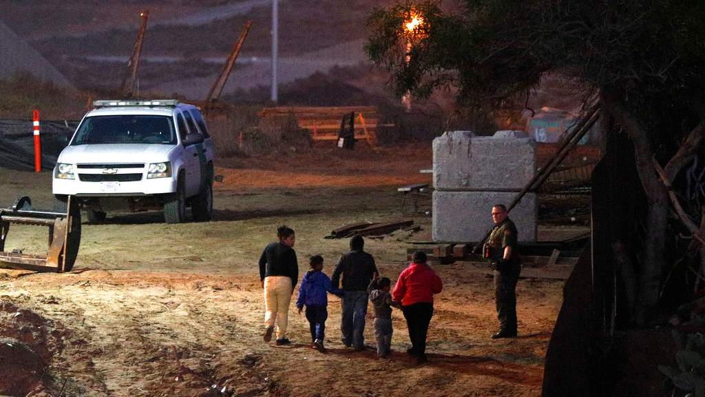 Migrants traveling with children walk up a hill to a waiting U.S. Border Patrol agent just inside San Ysidro, Calif., after climbing over the border wall from Playas de Tijuana, Mexico, Monday, Dec. 3, 2018. (AP Photo/Rebecca Blackwell)