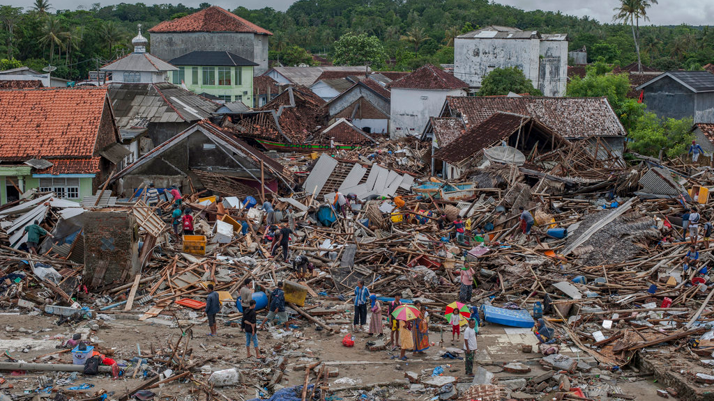 People inspect the damage at a tsunami-ravaged village in Sumur, Indonesia, Monday, Dec. 24, 2018. Doctors are working to help survivors and rescuers are looking for more victims from a deadly tsunami that smashed into beachside buildings along an Indonesian strait.