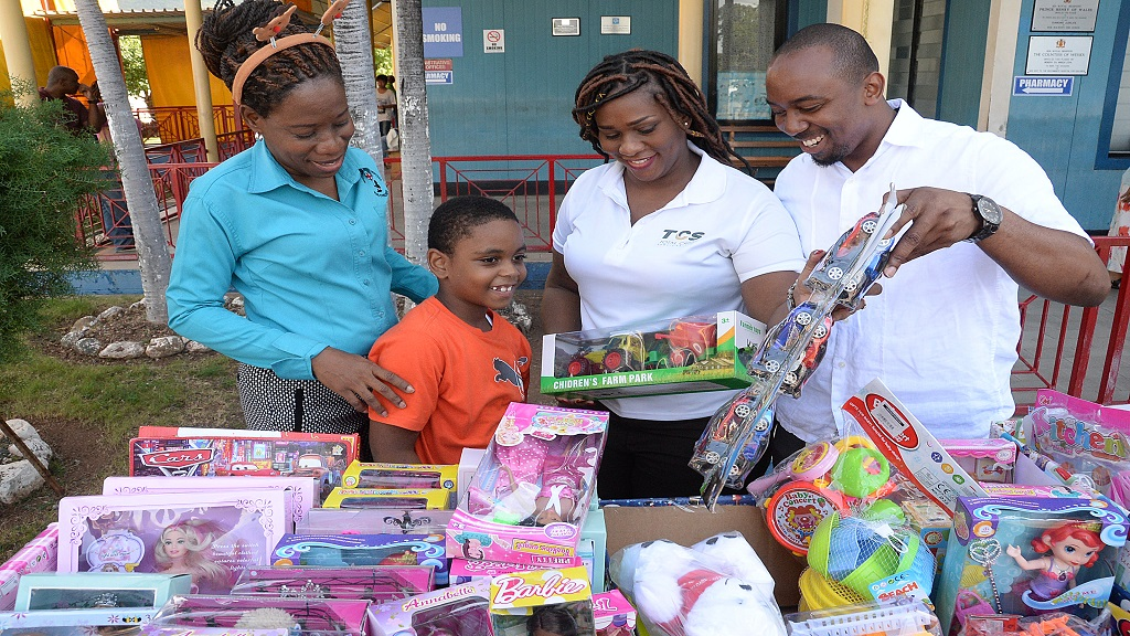 Geovanni Hall (second left), a patient at the Bustamante Hospital for Children, receives a toy from members of staff of Total Credit Services (TCS) Limited, Rashida Porteous-Sawyers (second right), assistant manager and Rashorn Ricketts (right), manager. Sharing in the moment is Jasmine Simmonds Henry, acting patient affairs manager at the Bustamante Hospital for Children.