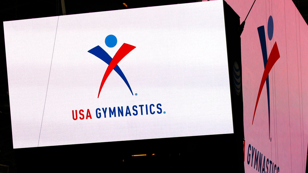 In this Feb. 26, 2014, file photo, the USA Gymnastics logo is displayed at AT&T Stadium during an news conference announcing in Arlington, Texas. (Ron Jenkins/Star-Telegram via AP)