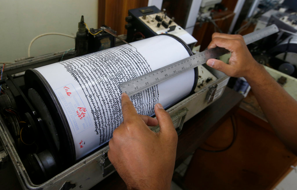An official looks a seismograph at an observation post near a recent volcanic eruption in Carita, Indonesia, Thursday, Dec. 27, 2018. Indonesia has widened the no-go zone around an island volcano that triggered a tsunami on the weekend, killing hundreds of people in Sumatra and Java. (AP Photo/Achmad Ibrahim)