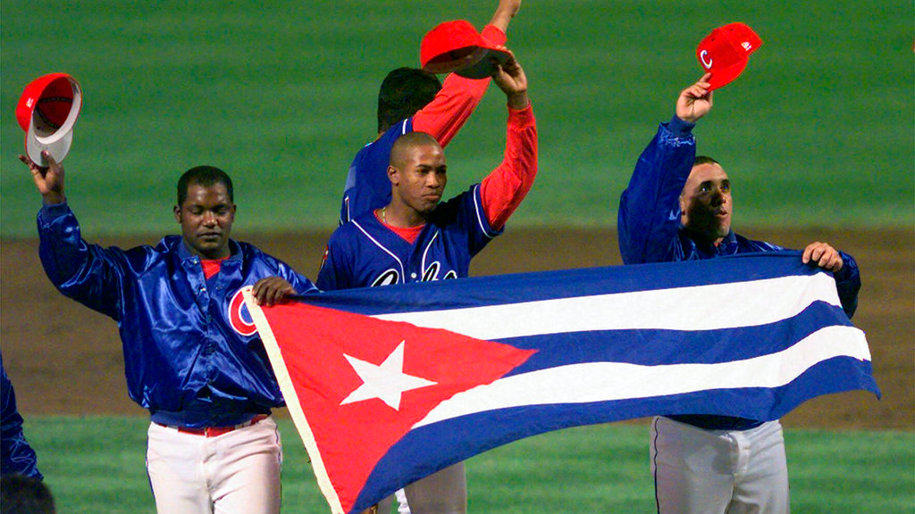 In this Monday, May 3, 1999 file photo, members of the Cuban baseball team carry their country's flag onto the field after a baseball game against the Baltimore Orioles at Camden Yards in Baltimore.