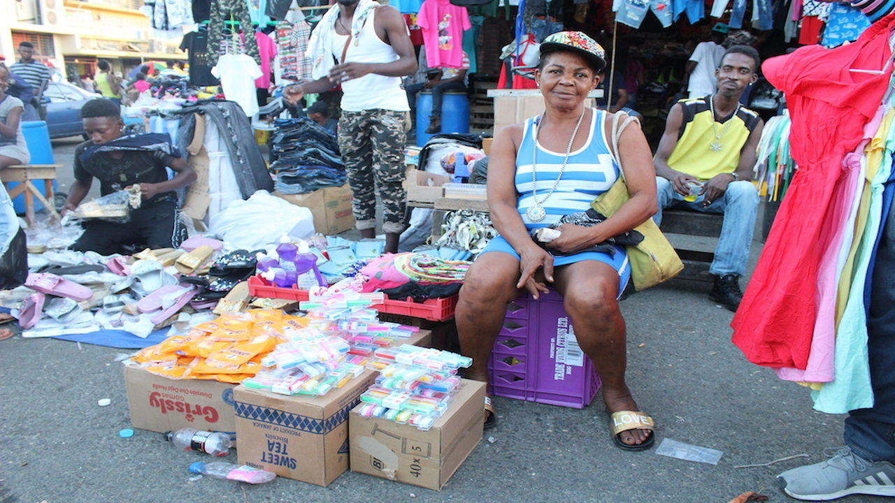A vendor points to her products in downtown Kingston on Thursday.