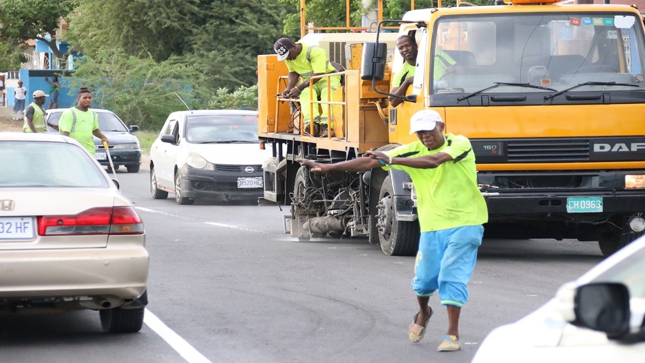 A member of a road marking team on duty directing traffic away from the team's activities along the new Three Miles bypass road in St Andrew on Sunday afternoon. 