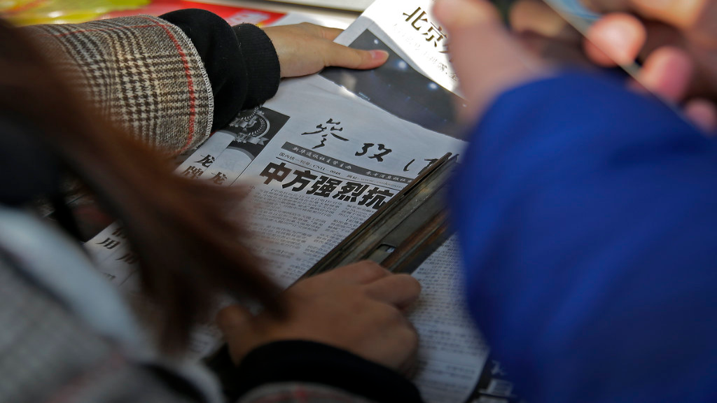 A woman takes a copy of a newspaper near another with the headline of China outcry against U.S. on the detention of Huawei's chief financial officer, Meng Wanzhou, at a news stand in Beijing, Monday, Dec. 10, 2018. China has summoned the U.S. ambassador to Beijing to protest Canada's detention of an executive of Chinese electronics giant Huawei at Washington's behest and demand the U.S. cancel an order for her arrest. (AP Photo/Andy Wong)