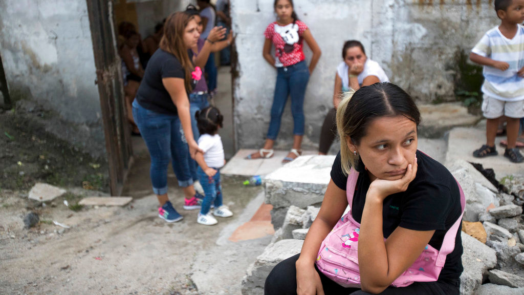In this Oct. 31, 2018 photo, relatives who attended the burial service of Wilmer Gerardo Nunez wait for a bus to transport them home, at a cemetery in San Pedro Sula, Honduras. About a week after Nunez left Honduras for the last time, he spoke to his mother, telling her to pray that everything would turn out well. A few weeks after that call Nunez disappeared. (AP Photo/Moises Castillo)