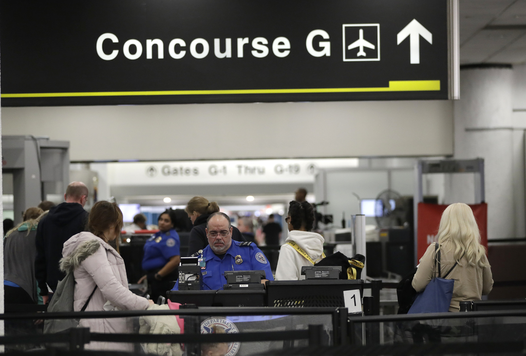 A Transportation Security Administration official works at the entrance to Concourse G at Miami International Airport.  (AP Photo)