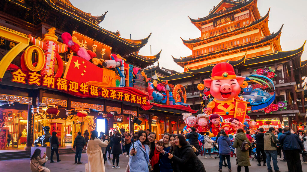 In this Jan. 17, 2019, photo, women take a selfie as others tour at the Yu Garden decorated with pig statues for Lunar New Year in Shanghai. China's 2018 economic growth fell to a three-decade low as activity cooled amid a tariff war with Washington. (Chinatopix via AP)
