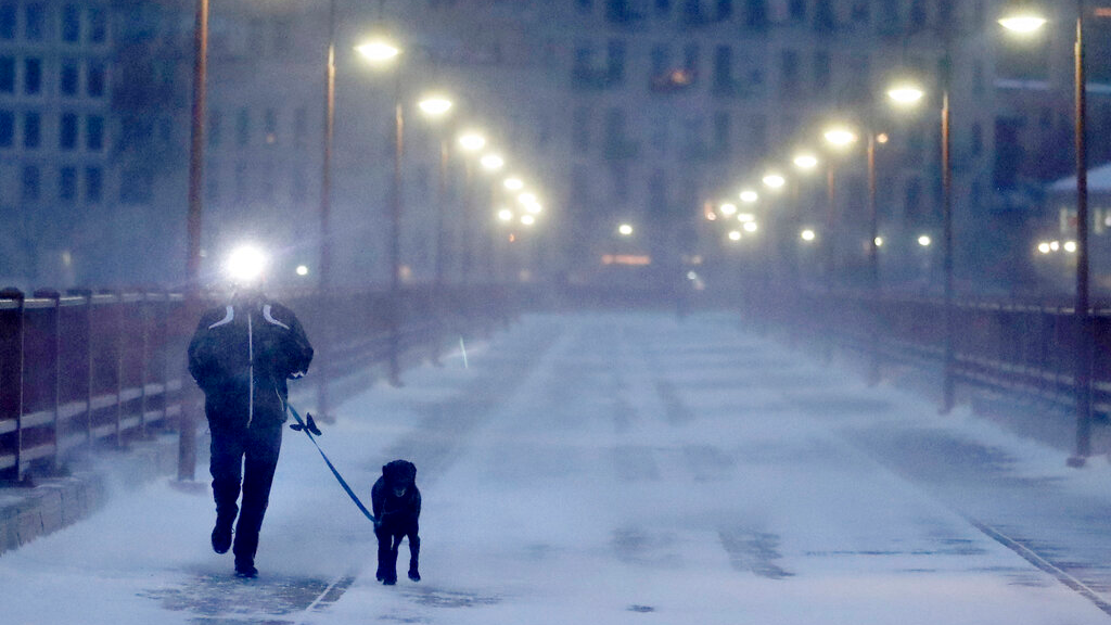 A runner and his dog brave frigid conditions while making their way east across the Stone Arch Bridge, Thursday, Jan. 24, 2019, in Minneapolis. The National Weather Service issued a wind child advisory overnight Thursday for Wisconsin, Minnesota, the Dakotas and several other states. (David Joles/Star Tribune via AP)