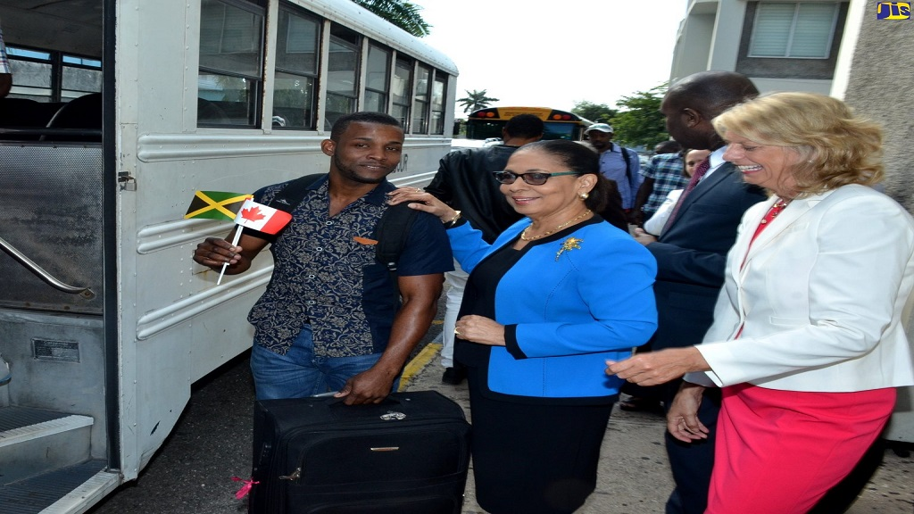 Minister of Labour and Social Security, Shahine Robinson (centre) and High Commissioner of Canada to Jamaica,  Laurie Peters (right), bid farewell to Jermaine Wilson, as he boards the bus that will take him and other Jamaicans to the airport for departure to Canada recently. (Photo JIS)