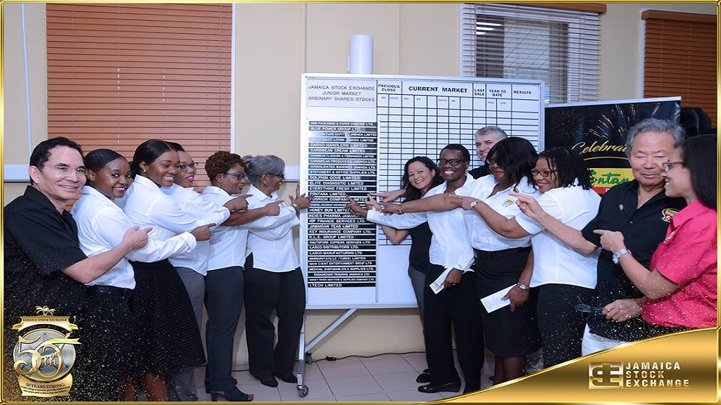 Fontana staff and other company executives pose for a photo at the Jamaica Stock Exchange's trading board before following the company's listing. Photo via JSE, Facebook.