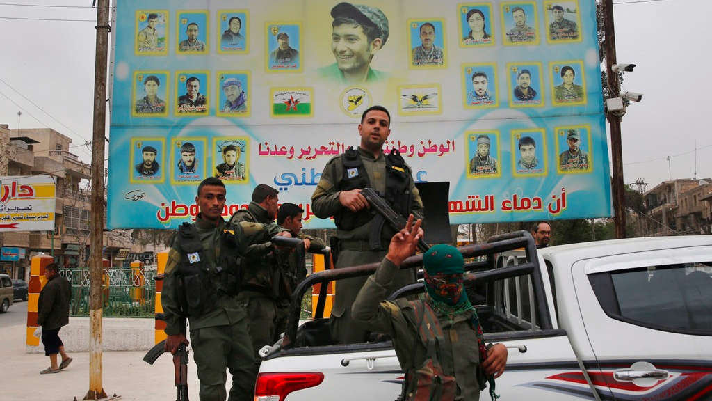 In this photo taken on Wednesday, March 28, 2018, members of the Kurdish internal security forces stand on their vehicle in front of a giant poster showing portraits of fighters killed fighting against the Islamic State group, in Manbij, north Syria. The planned U.S. troop withdrawal opens a void in the north and east of Syria, and the conflicts and rivalries among all the powers in the Middle East are converging to fill it. (AP Photo/Hussein Malla, File)
