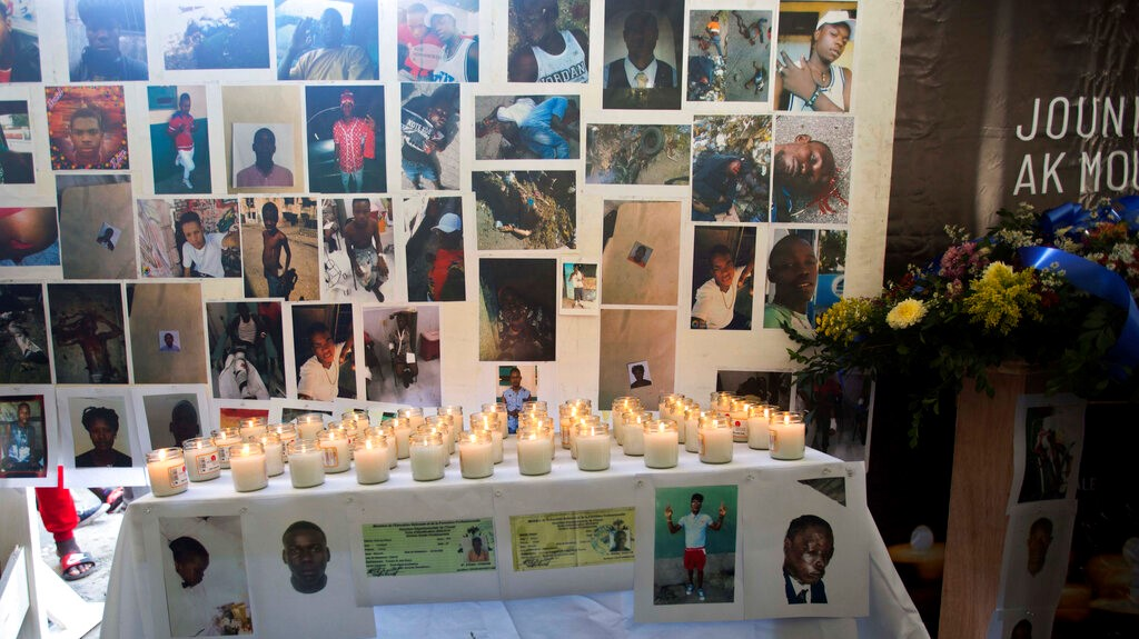 In this Dec. 13, 2018 photo, pictures, candles and flowers decorate an altar for the massacre victims during a memorial in the La Saline slum of Port-au-Prince, Haiti. (AP Photo/Dieu Nalio Chery)