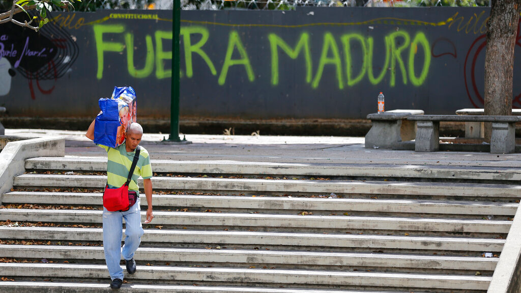 "A man walks past graffiti on the wall of a vacant lot that reads in Spanish: ""Get out Maduro,"" referring to President Nicolas Maduro in Caracas, Venezuela, Thursday, Jan. 24, 2019. (AP Photo/Fernando Llano)"