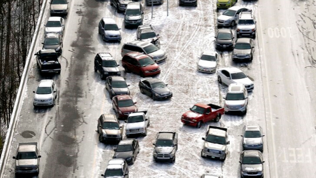 In this Jan. 29, 2014 aerial file photo, abandoned cars at I-75 headed northbound near the Chattahoochee River overpass are piled up in the median of the ice-covered interstate after a winter snow storm, in Atlanta. (AP Photo/David Tulis, File)
