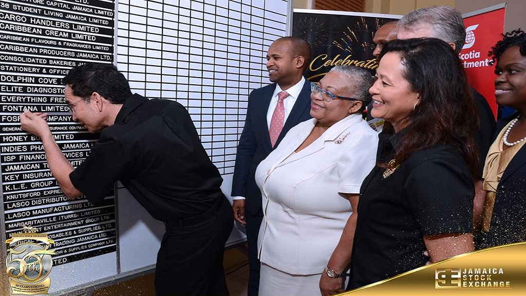 Fontana chairman Kevin O'Brien Chang places the company's name card on the JSE trading board as JSE Managing  Director Marlene Street Forrest (centre), Scotia Investments VP Dylan Coke (left) and Fontana CEO Anne Chang (right) and others look on. Photo via JSE's facebook page.