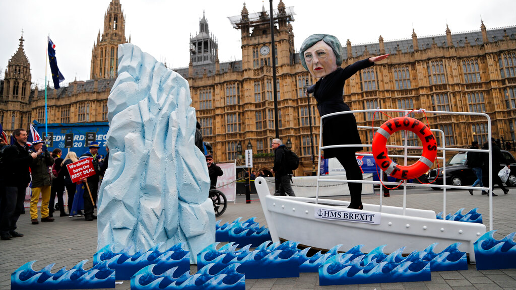An activist from Avaaz wears a mask of Britain's Prime Minister Theresa May as Pro-European demonstrators protest opposite the Houses of Parliament in London, Tuesday, Jan. 15, 2019.